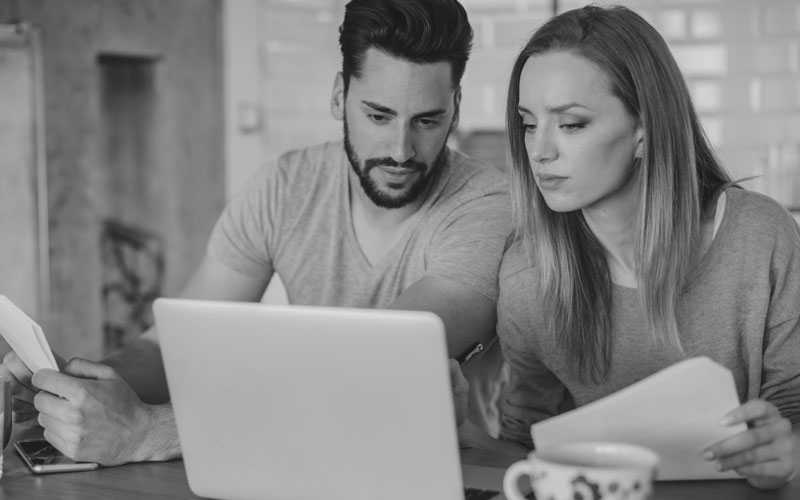 Couple looking at lap top and looking concerned the home report has a category 3 stamp